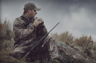 man using binoculars for hunting